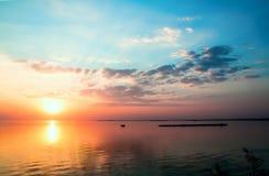 Bewölkter Himmel des drastischen schönen Sonnenuntergangs über einer Oberfläche des LAK Stockfoto