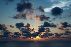 Bewölkter Himmel mit Sonnenstrahl auf den Ozean zur Sonnenuntergangzeit Lizenzfreies Stockfoto