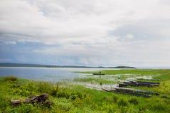 Bewölkter Himmel mit Wasser und Fischerbooten Stockfotografie
