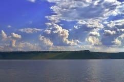 Bewölkter Himmel und Fluss in der grünen Landschaft Lizenzfreies Stockbild