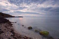 Bewölkter Sonnenaufgang auf Meer-felsigem Ufer Stockfotografie