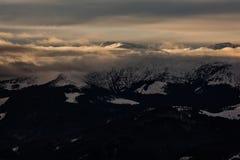 Bewölkter Sonnenuntergang über den schneebedeckten Spitzen der Karpaten Lizenzfreies Stockfoto