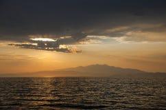 Bewölkter Sonnenuntergang über einer Insel Stockfoto