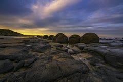 Bewölkter Sonnenuntergang an Moeraki-Flusssteinen über Otago-Küstenlinie, Südinsel, Neuseeland stockbild