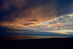 Bewölkter Sonnenuntergang am Strand Stockbild