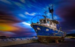 Bewölkter Sonnenuntergang und Boot Stockfotografie