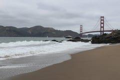 Bewölkter Tag auf dem Strand, der Golden gate bridge betrachtet stockbild