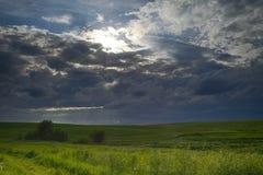 Bewölkter Tag mit einer kleinen Sonne, die über grünen Feldern scheint stockfoto
