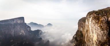 Bewölkter Tian Men Mountains in Zhangjiajie mit rotem betendem Gewebe Stockfoto