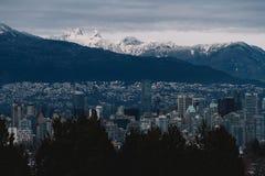 Bewölktes Stadtbild mit Bergen im Schnee im Hintergrund stockbilder