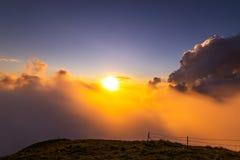 Bew?lkter Sonnenuntergang in den Bergen stockfotos