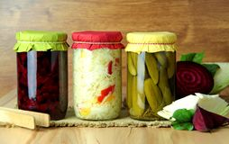 Bewaarde groenten Bieten, kool en komkommers in een glaskruiken Houten achtergrond stock afbeeldingen