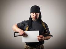 Bewaffneter Bandit hält Weißbuch Stockbilder