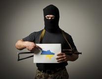 Bewaffneter Bandit hält Weißbuch mit einer Frage über Zukunft von Großbritannien Lizenzfreies Stockbild