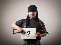 Bewaffneter Bandit hält Weißbuch mit Fragekennzeichen Stockfoto