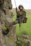 Bewaffneter Militäralpinist, der am Seil hängt Lizenzfreies Stockfoto