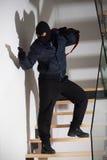 Bewaffneter Räuber auf Treppe Stockfoto