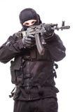 Bewaffneter Terrorist in der schwarzen Maske und schwarzen in der Uniform, die mit einem Gewehr zielt Porträt von gutem oder von  stockfoto