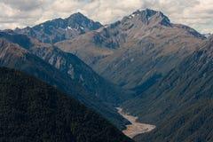 Bewaldete Steigungen in den südlichen Alpen Stockfotos