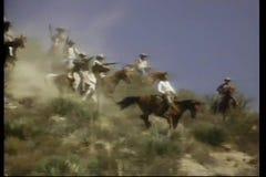 Bewapende mensen bij horseback het berijden onderaan berg stock video