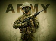 Bewapende militair met beschadigde muurachtergrond stock fotografie