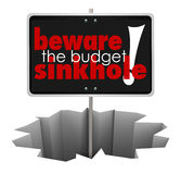Beware the Budget Sinkhole Sign Hole Money Trouble Bankruptcy. Beware the Budget Sinkhole words on a sign in a hole, crack or chasm to symbolize money trouble Stock Image