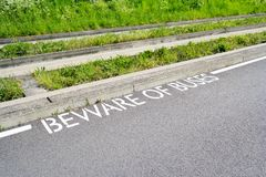 Beware of Buses Sign next to Guided Busway Tracks. Copy space provided royalty free stock photography