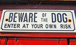 Beware of the dog. Sign against a weathered background royalty free stock photos