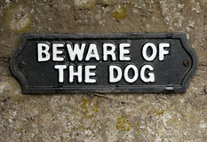 Beware of the dog. Sign screwed onto stone royalty free stock images