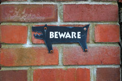 Beware of the dog. A black sign in a red brick wall in a shape of a dog with the word BEWARE Royalty Free Stock Photography