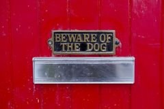 Beware of Dog Sign On Front Red Door of House with Letterbox for Postman. Beware of dog sign on front gate of house above letter box royalty free stock image