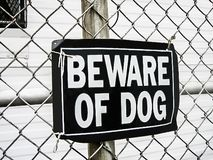 A beware of dog sign on a mesh fence as a safeguard warning of dangerous rottweiler attack if trespassing stock images