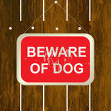 Beware of a dog sign on a wooden fence Stock Image