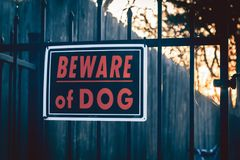 Beware of Dog Sign. On wrought iron gate with wooden fence, trees and sunrise in background royalty free stock images
