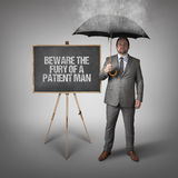 Beware the fury of a patient man text on blackboard with businessman Stock Images
