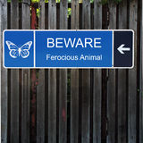 Beware Horizontal Blue Sign on Old Wood Fence. A three section signs with blue background and wite lettering and buttterflly and arrow on a tall old wood fence Royalty Free Stock Photo