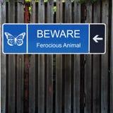 Beware o sinal azul horizontal na cerca de madeira velha foto de stock royalty free