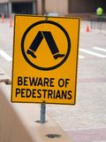 Beware of Pedestrians Sign. A black and yellow warning sign near a construction site; beware of pedestrians stock image