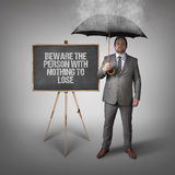 Beware the person with nothing to lose text on blackboard with businessman Royalty Free Stock Image