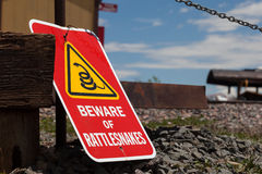 Beware of Rattlesnakes. A sign warning people to beware of rattlesnakes attached to a wooden fence in front of railroad tracks with a shovel leaning up against Stock Photo