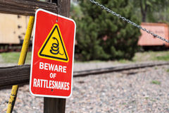 Beware of Rattlesnakes. A sign warning people to beware of rattlesnakes attached to a wooden fence in front of railroad tracks with a shovel leaning up against Stock Photography
