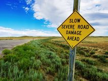 A beware of road damage sign on lonely road in Wyoming. Royalty Free Stock Photos