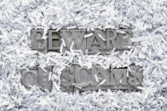 Beware of scams. Phrase made from metallic letterpress type inside of shredded paper heap stock images
