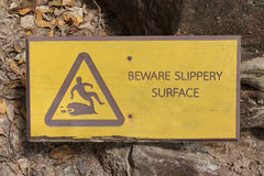 Beware slippery surface sign. Placed on natural path with rocks and stones stock photo