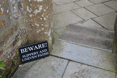 Beware slippery and uneven paths sign. Royalty Free Stock Photography