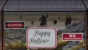 Beware of Zombies Happy Halloween. This video features zombies walking forward in a field behind a wire fence with an animated Happy Halloween message stock footage