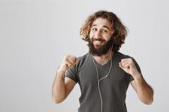 Beweeg uw heupen in ritme van muziek Positieve blije oostelijke mens die met baard en krullend haar dichtgeklemde vuisten, het gl stock afbeelding