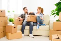 Bewegen auf eine neue Wohnung Glückliche Familienpaare und -Pappschachtel Lizenzfreie Stockfotos