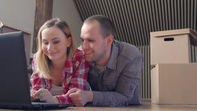 Bewegen, Ausgangs-, Technologie- und Paarkonzept - lächelndes Paar mit dem Laptop, der auf Boden im neuen Haus sitzt stock video footage