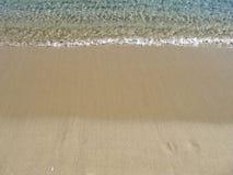Bewegen Sie auf einen sandigen Strand, auf Sommerferien wellenartig Stockfotos
